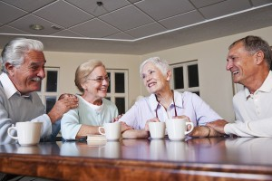 Two senior couples drinking coffee together in community center.
